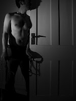 topless man waiting in the dark behind the door with rope