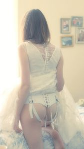 Woman in wedding dress and wearing a strap on