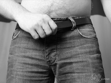 Man pulling leather belt through trouser loops