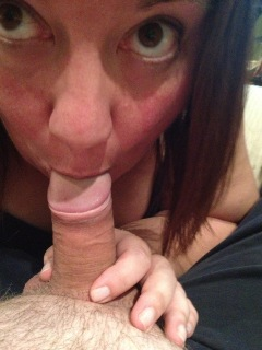 Woman looking up at camera while sucking cock