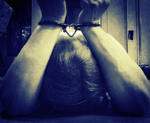 Woman handcuffed with bowed head