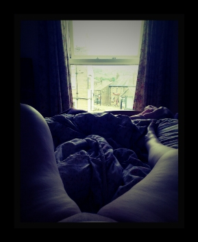 Woman laying in bed watching the world outside her window