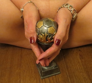 woman with football trophy between her legs