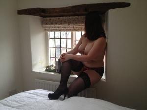 Woman in window seat in lingarie