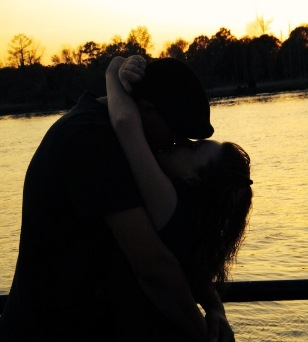 Couple kissing on the pier at sunset