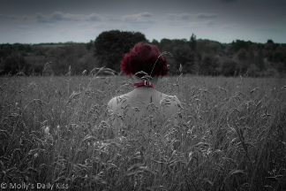 Woman with red hair sitting in field of grass