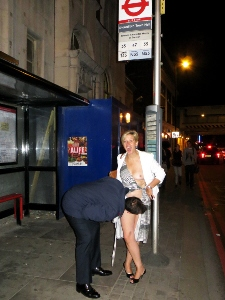 Woman flashing boobs and laughing at bus stop