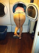 Woman with head in washing machine showing of bum