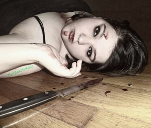 Woman laying on floor with bloody knife