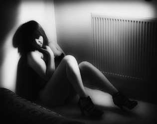 Woman sitting on floor in lingerie by the bed