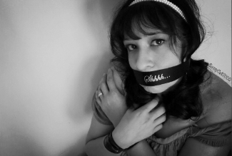 Woman with mouth gagged and pleading eyes