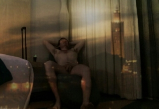 Man reclining naked in hotel room