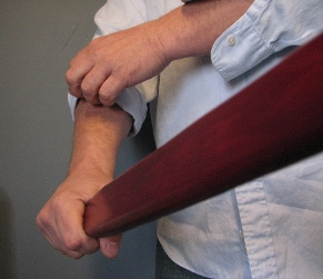 Man rolling up sleeves holding a wooden paddle