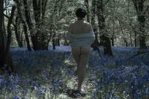 Woman walking naked in bluebells