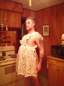 Man wearing frilly apron and nothing else
