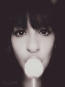 Sassy cat portrait licking lollipop