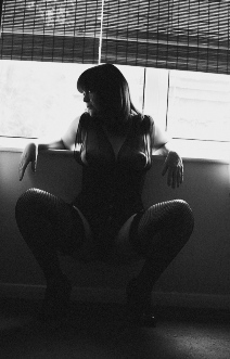 Black and white of women in corset crouching down