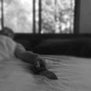 man lying in bed holding a knife
