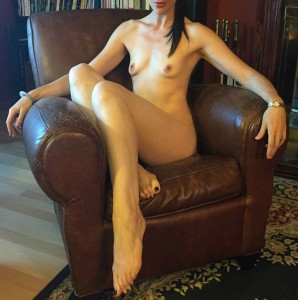 Malin sitting naked in leather chair
