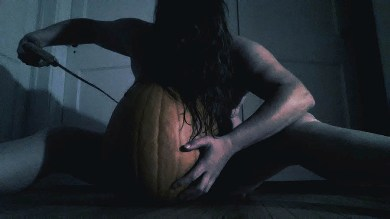 Woman carving pumpkin naked