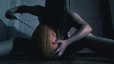 Woman carving pumpkin naked