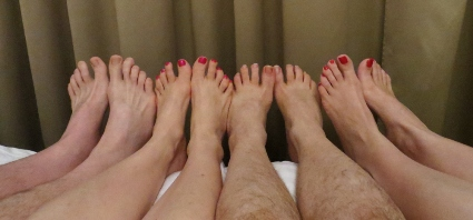 Row of four feet lined up in bed