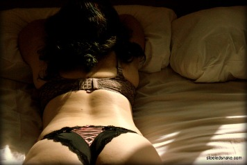 Woman laying on bed in sunlight in lingerie