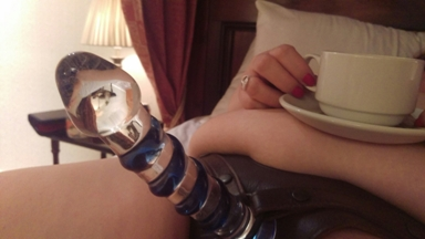 Honey wearing strap on with glass dildo and cup of tea resting on her belly