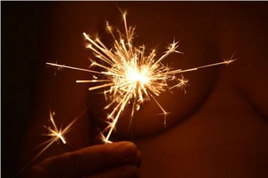 Sparkler in front of naked breast