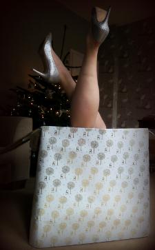 Woman in silver high heels inside Christmas box