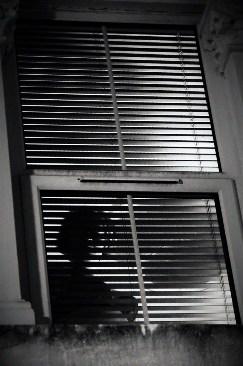 Woman standing in window wearing bra