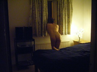 Naked man looking out of bedroom window
