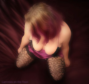 M kneeling on the floor in purple lingerie with matching purple highlight in hair