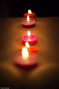 Line of tealight candles down a womans back