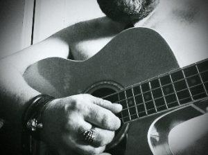 Naked man playing guitar