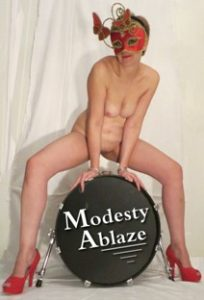Woman sitting naked astride a base drum