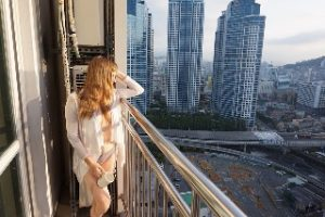 Woman standing on balcont in morning sun with city view sinful sunday sex