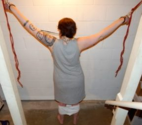 Woman tied up at bottom of basement stairs