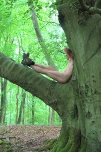 Nude man wearing walking boots sitting in tree