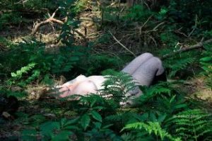 Woman laying naked in the woods