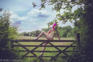 Woman sitting naked on gate