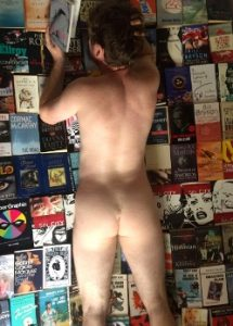 man laying naked on books sinful sunday