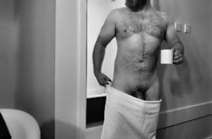 Man in towel with cup of coffee