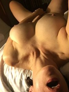 woman laying nude on bed touching herself