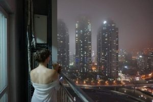 Woman on Balcony overlooking night time city