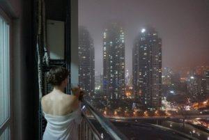 Woman on Balcony overlooking night time city