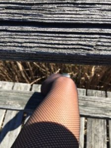 Woman in fishnet stockings with sunshining on her leg