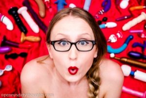 Penny in glasses with bright red lipstick looking into the camera surrounded by a background of sex toys
