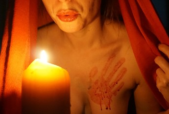 Woman with bloody hand print on her breast blowing out candle