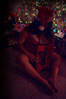 Woman in sexy santa outfit under the christmas tree